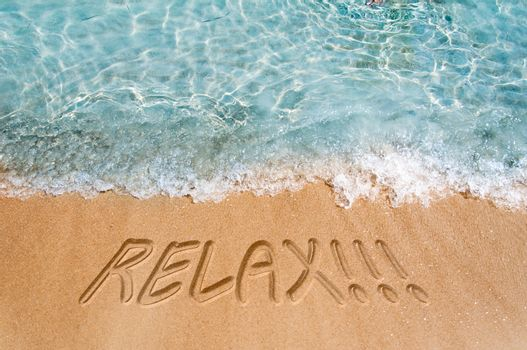 Relax sign on the beach sand