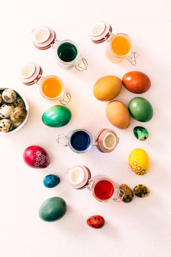 Easter eggs and jars with colored liquid from above on white background