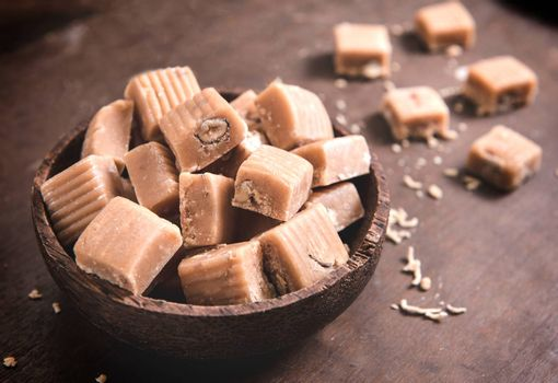 Caramel bonbons with almonds in wooden bowl,selective focus