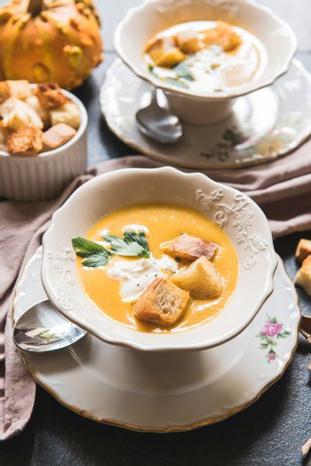 Served homemade pumpkin soup with milk cream and croutons bread in bowl,selective focus