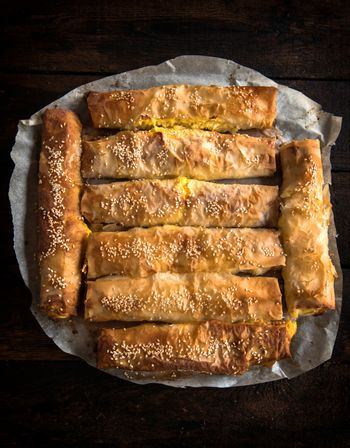 Homemade cheese pie sticks on wooden background from above
