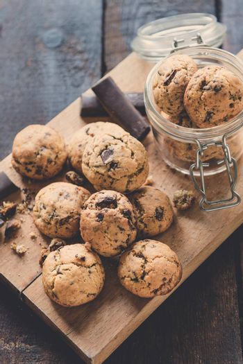 Mini homemade chocolate chip cookies on wooden background, selective focus
