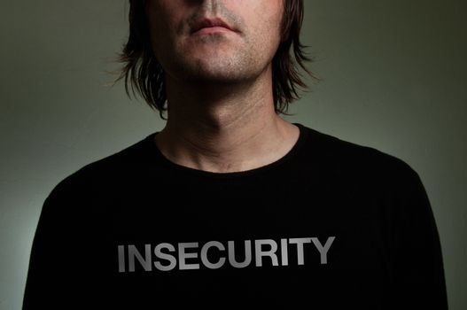 """Man wearing a black shirt with """"Insecurity"""" title on his chest. Shiness, insecurity, solitude concept image."""