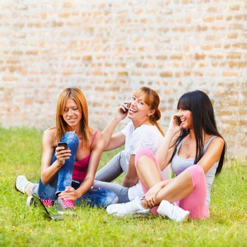 Three young beautiful girls communicate with mobile phone outdoor