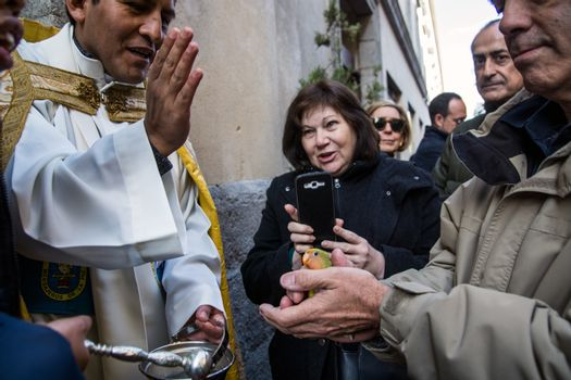 SPAIN, Madrid: A man holds his pet bird while it's being blessed by a priest outside the church of San Antón in Calle de Hortaleza in Madrid on Saint Anthony's day, the patron saint of animals, on January 17, 2016.