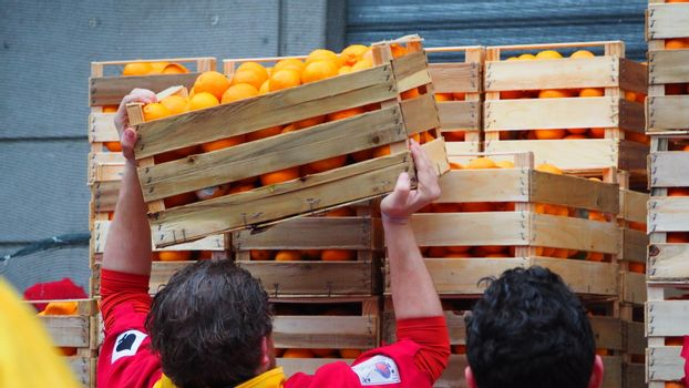 ITALY, Ivrea: People unload crates of oranges on February 7, 2016.An estimated 7,000 people turned out to pelt each other at the historic festival. 70 people were injured by the flying fruit.