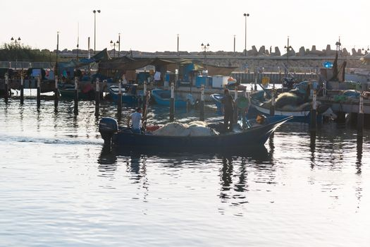People in a boat float away from the harbor