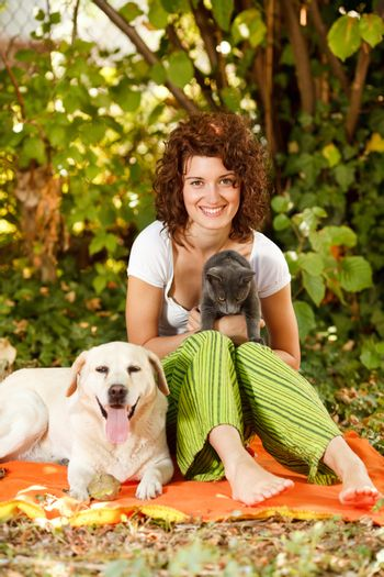 Young beautiful woman relaxing in nature with pets