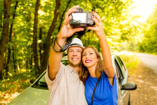 Young travelers standing before a car in the forest and taking photo of themselves.
