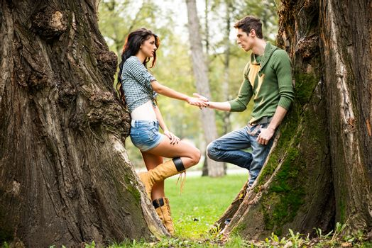 Young and pretty girl and guy at park leaning against a tree trunk, facing each other holding hands.