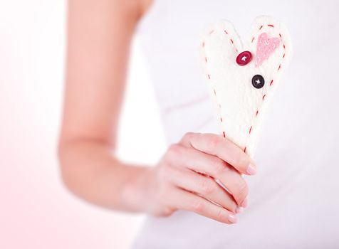 Woman holding in hand handmade sewn soft heart over white background, body part, great gift for Valentines day, love concept