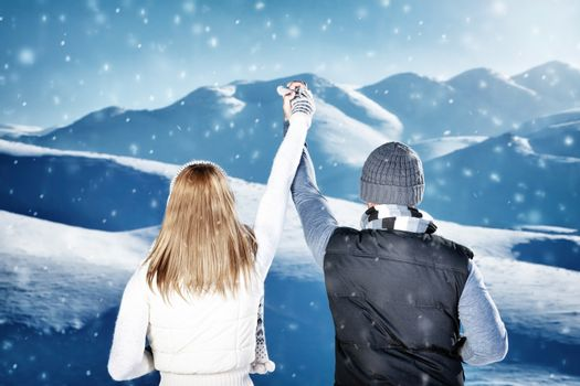 Happy couple in winter mountains, rear view of a young family holding hands and enjoying beautiful view, spending active winter holidays
