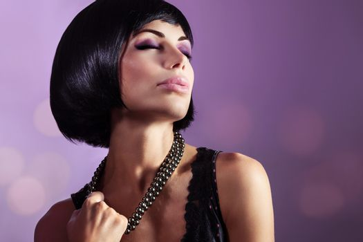 Sensual portrait of a beautiful woman with closed eyes over purple background, gorgeous lady with perfect hairstyle and makeup breaking her beads, fashion look