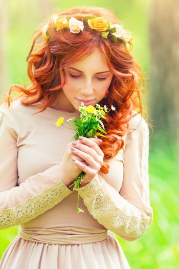 Portrait of a beautiful romantic girl enjoying aroma of a gentle wild flowers in the spring park, sensual fashion look of the forests nymph