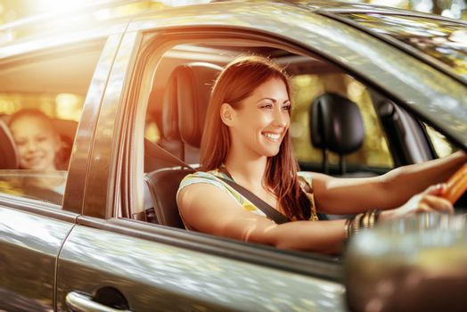 Young beautiful smiling woman driving a car.  Her cute daughter sitting on rear and enjoying.