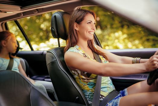 Young beautiful smiling woman with driving a car.  Her cute daughter sitting on rear and enjoying.