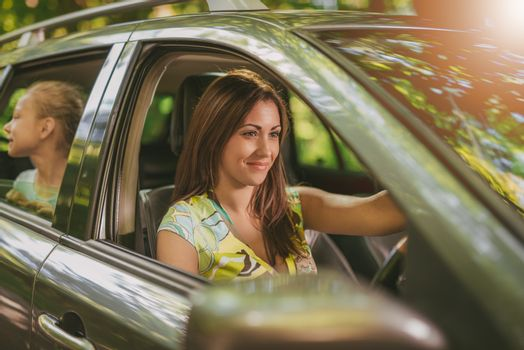 Young beautiful smiling woman driving a car.  Her cute daughter sitting on rear and looking the environment.