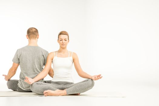 Young couple practicing yoga sitting in lotus position on yoga mats