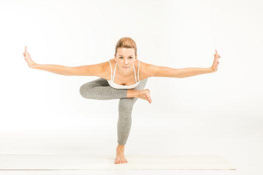 Woman practicing yoga performing squatting pigeon pose on yoga mat