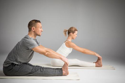 Couple practicing yoga sitting in Paschimottanasana (Seated Forward Bend) yoga position