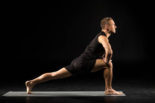 Side view of young man practicing yoga and stretching on yoga mat