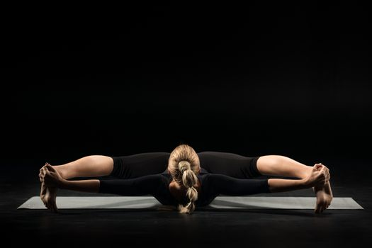 Woman pacticing yoga lying on her back on yoga mat