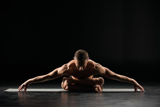 Young man practicing yoga while sitting in lotus position on yoga mat
