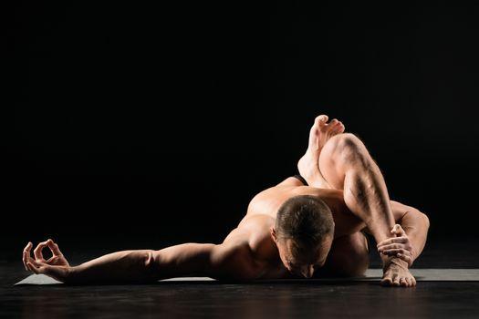 Young man practicing yoga in asana on yoga mat