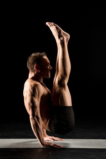 Young athletic man practicing yoga performing handstand on yoga mat