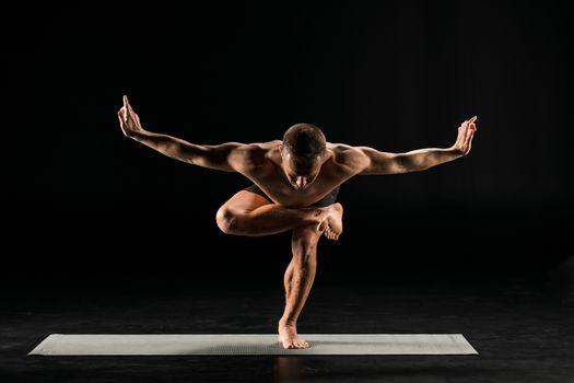 Man practicing yoga performing squatting pigeon pose on yoga mat