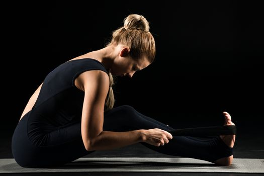 Side view of young woman practicing yoga and stretching with yoga strap