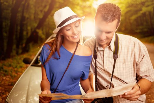 Young beautiful couple standing leaning at car in the forest and looking a map.