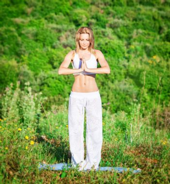 Woman doing exercise yoga outdoors in fresh green park on mountain background, peaceful standing in position and meditating, healthy lifestyle