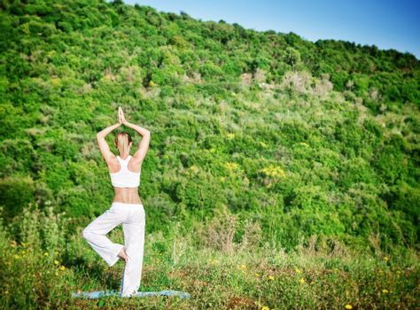 Back side of sportive woman doing fitness exercise outdoor on beautiful green mountain background, enjoying yoga and zen balance