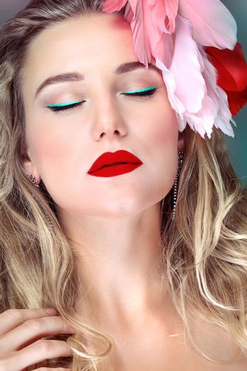 Closeup portrait of a beautiful woman with closed eyes with bright makeup and feather accessories, fashion model glamour look
