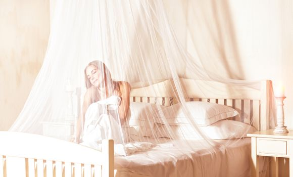 Gentle woman wakes up from sleep in the morning in luxury spa hotel, sitting on the bed under valance with closed eyes of pleasure