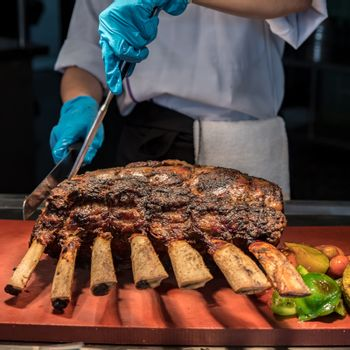 Chef Carving prime rib of  roast Wagyu beef