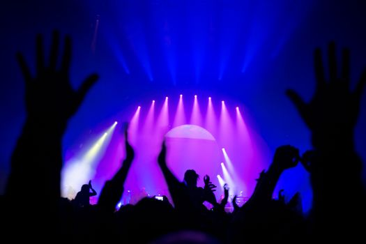 Silhouette of people partying in nightclub, raised up hands enjoying great musical show, live music performance, celebrating New Year