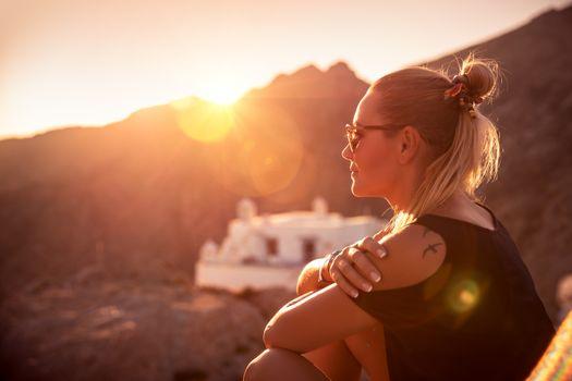 Beautiful woman enjoying travel, wonderful place on sunset light, girl sitting on the mountains near the monastery, happy summer holidays
