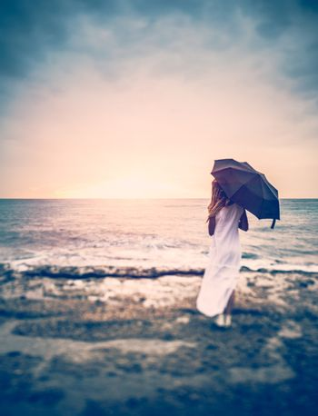 Sadness concept, rear view of a woman with umbrella on the beach, girl in overcast weather looking on the stormy sea, loneliness