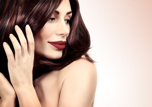 Closeup portrait of a beautiful woman with red lips and perfect shiny hair over clear background, fashion beauty salon