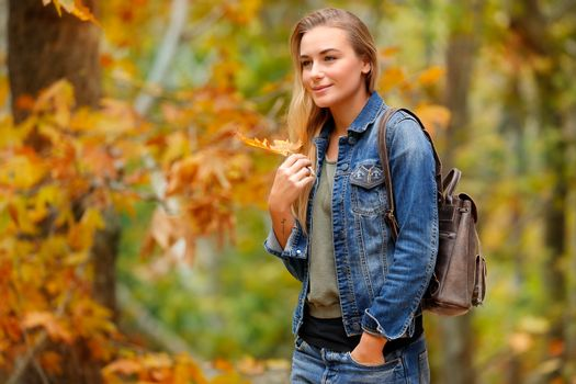 Beautiful woman walking in autumn park with dry tree leaf in hand, enjoying fall weather