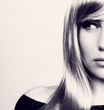 Closeup portrait of a beautiful blond woman, black and white photo of a women's half face over clean background, beauty and fashion concept