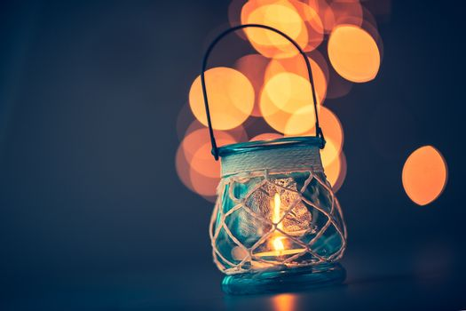 Romantic candlelight atmosphere, beautiful vintage candle lantern burning on mild blurry lights background, beauty and romance concept