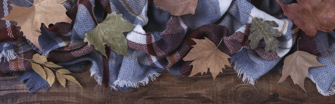 Blanket and autumn leaves on old wooden background Vintage toning seasonal relax concept banner