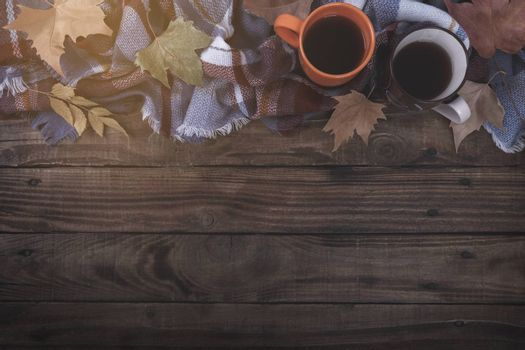 Twho cups of hot coffee or tea blanket and autumn leaves on old wooden background vintage toning Seasonal relax concept