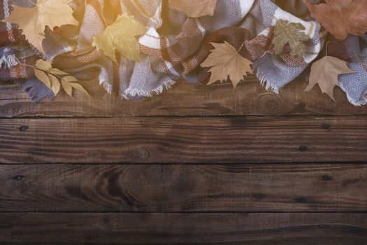 Blanket and autumn leaves on old wooden background Vintage toning seasonal relax concept copy space