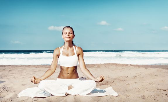Pretty woman with pleasure meditating outdoors, sitting on the beach in lotus pose with closed eyes and doing yoga asana, peace and zen balance concept