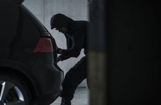 Masked Caucasian Car Thief Stealing Modern Vehicle. Transportation Theme.