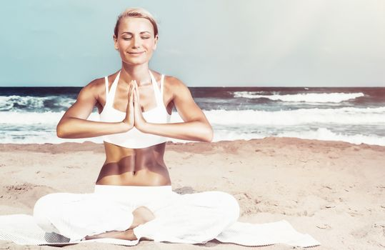 Pretty woman sitting with closed eyes in lotus pose on the beach, meditating on the coast of the sea, enjoying peaceful summer vacation, happy and healthy lifestyle, zen balance